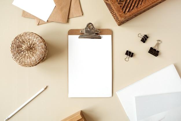 Bloco do tablet da área de transferência com folha de papel em branco. espaço de trabalho da mesa do escritório em casa do artista. camada plana, vista superior