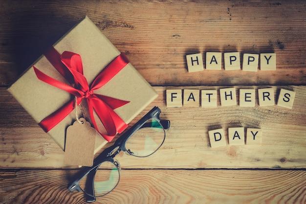 Bloco feliz do dia do pai e caixa de presente com óculos em fundo de madeira.
