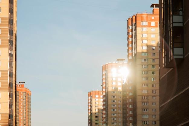 Bloco residencial moderno de edifícios de apartamentos com fachada de edifícios planos contra o céu azul claro. imóveis urbanos e complexos de edifícios para pessoas. conceito de renovação habitacional. copie o espaço