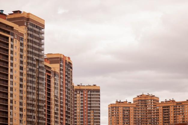 Bloco residencial moderno de edifícios de apartamentos com fachada de edifícios planos contra o céu azul claro. imóveis urbanos e complexos de edifícios para pessoas. conceito de renovação habitacional. copie o espaço Foto Premium
