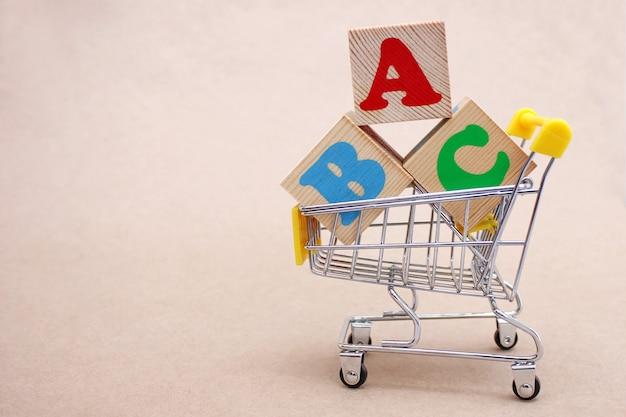 Blocos abc com letras em inglês em um carrinho de compras de brinquedo