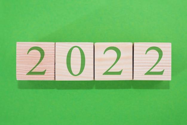 Blocos cúbicos de madeira 2022 em um fundo verde.