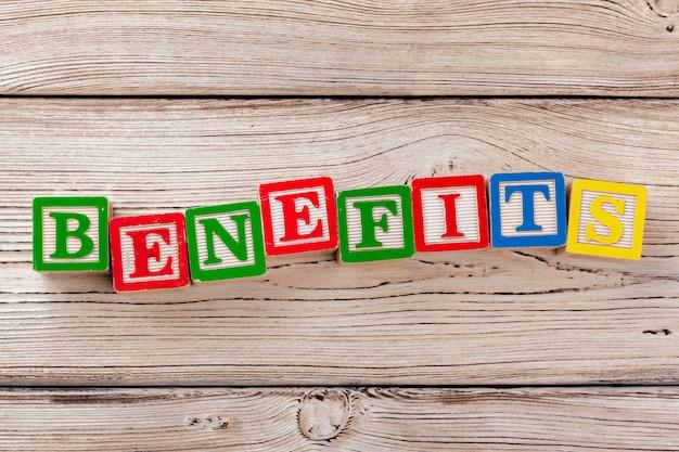 Blocos de brinquedo de madeira com o texto: benefícios