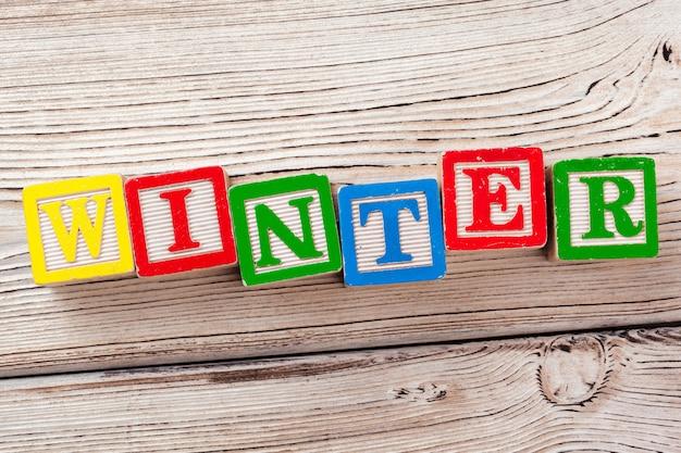 Blocos de brinquedo de madeira com o texto: inverno