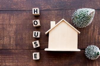 Blocos de carta de casa perto do modelo imobiliário com dois árvore de Natal no cenário texturizado de madeira