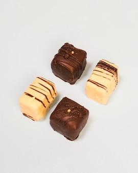 Blocos de chocolate branco e escuro, dispostos em fundo branco