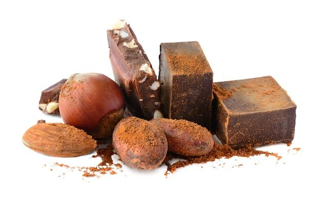 Blocos de chocolate com grãos de cacau e nozes isolados no fundo branco
