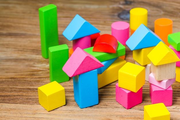 Blocos de construção em fundo de madeira, blocos de construção coloridos de madeira