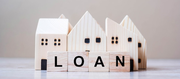 Blocos de cubo de empréstimo com modelo de casa de madeira no fundo da tabela.