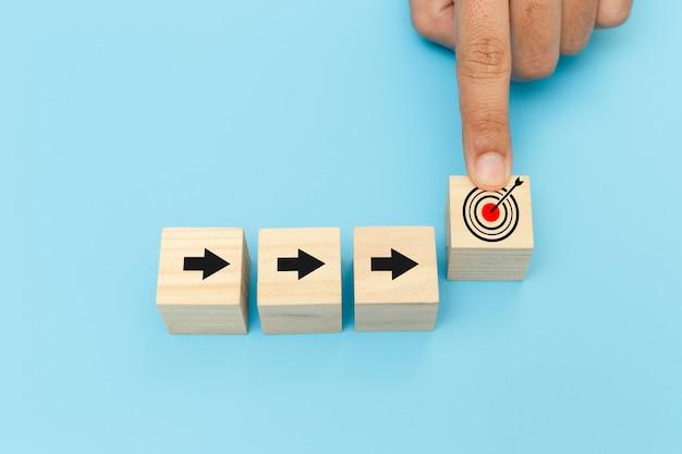 Blocos de cubo de madeira com símbolos de seta e alvo, mãos do dedo do homem apontando blocos de cubo de madeira de seleção com ícone de objetivo. classificação e classificação do conceito de negócio.