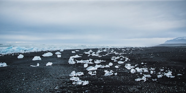 Blocos de gelo gigantes destacados dos icebergs na costa de uma praia islandesa.