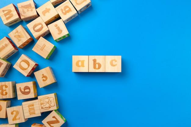Blocos de madeira alfabeto colorido, configuração plana, vista superior.