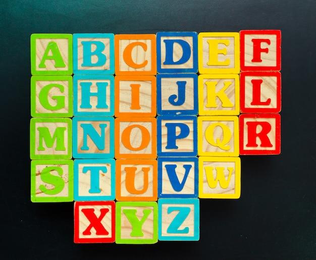 Blocos de madeira alfabeto com letras na placa de madeira