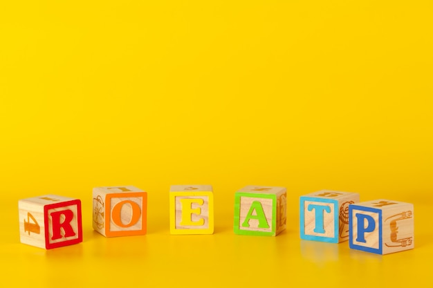 Blocos de madeira coloridos com letras em um fundo de cor amarela