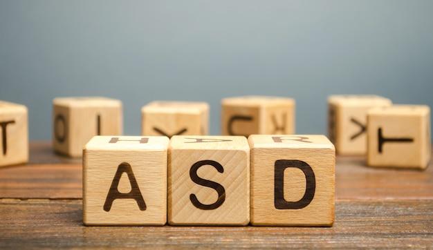 Blocos de madeira com a palavra asd - transtorno do espectro do autismo. distúrbio neurológico e do desenvolvimento