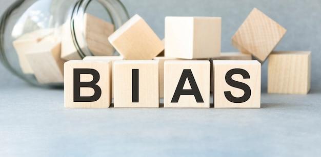 Blocos de madeira com a palavra bias. preconceito. opiniões pessoais. preconceito