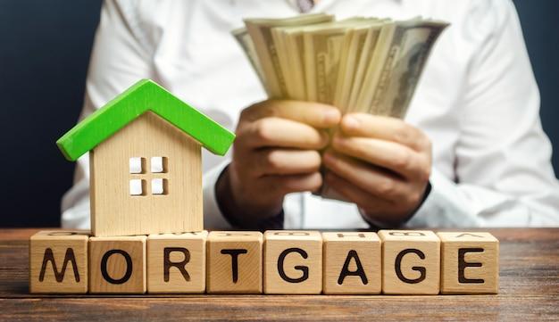 Blocos de madeira com a palavra hipoteca e dinheiro