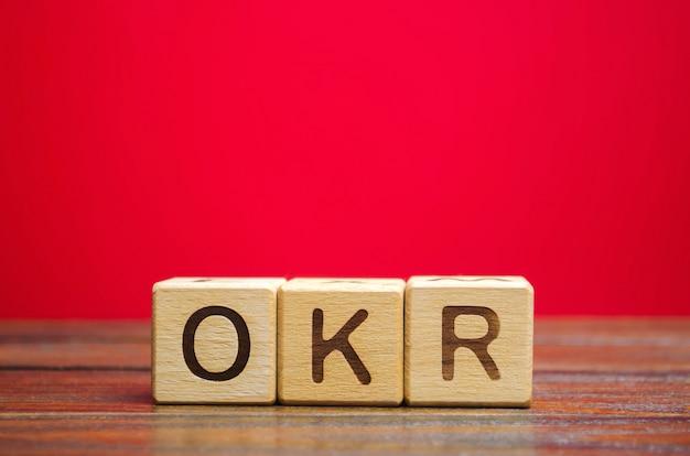 Blocos de madeira com a palavra okr (objetivos e principais resultados). objetivos da equipe e individuais.
