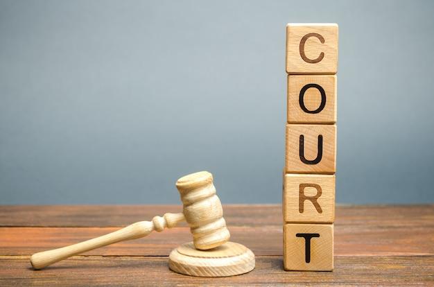 Blocos de madeira com a palavra tribunal e martelo de um juiz. solução de controvérsias