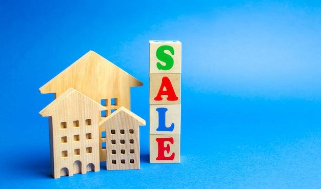 Blocos de madeira com a palavra venda e casas em miniatura de madeira.