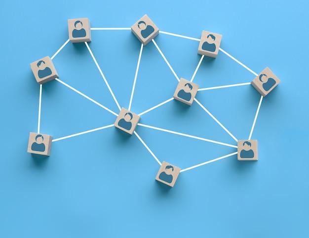 Blocos de madeira com ícone de pessoas interligados por linhas brancas sobre fundo azul. cooperação, trabalho em equipe, conceito de treinamento empresarial. conexões sociais, juntando-se para resolver tarefas