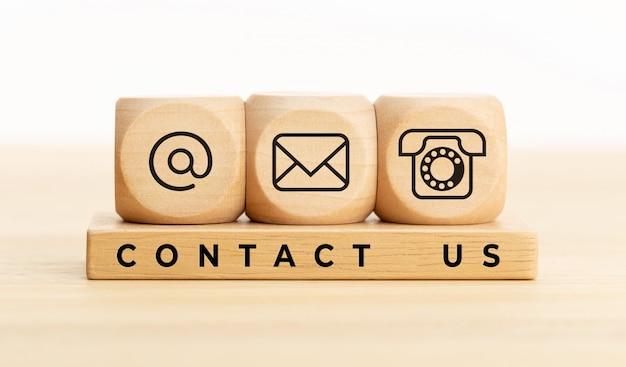 Blocos de madeira com ícones e texto de e-mail, correio e telefone.