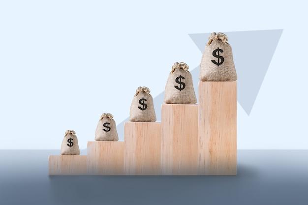 Blocos de madeira com sacos de dólares e seta para cima, crescimento financeiro, aumento da taxa de juros, conceito de inflação.