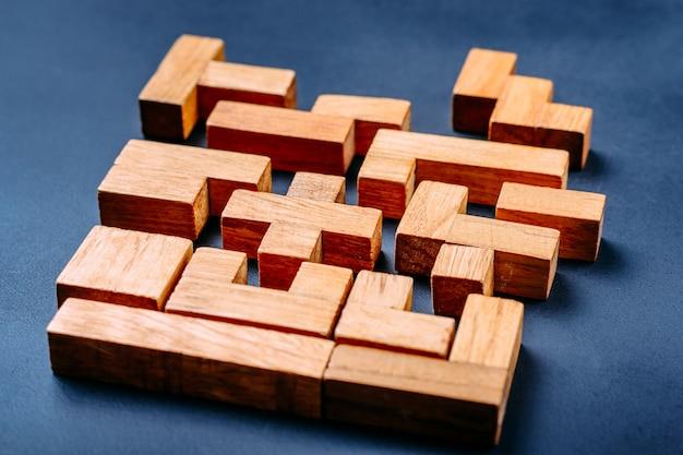 Blocos de madeira de diferentes formas geométricas em um fundo escuro.