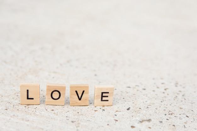 Blocos de madeira de texto soletrando a palavra amor no piso de concreto