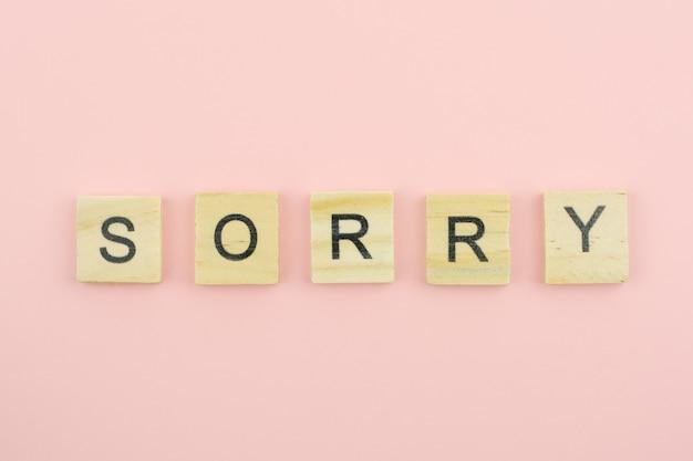 Blocos de madeira de texto soletrando a palavra desculpe no fundo rosa
