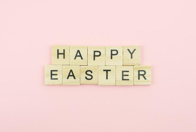 Blocos de madeira de texto soletrando a palavra feliz páscoa em fundo rosa