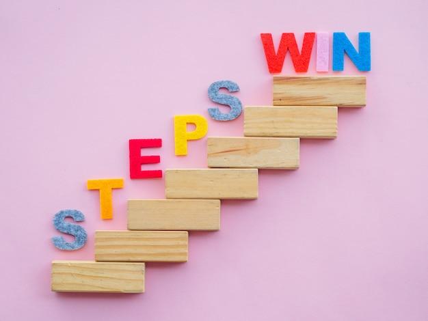 Blocos de madeira em forma de escada com passos para ganhar texto