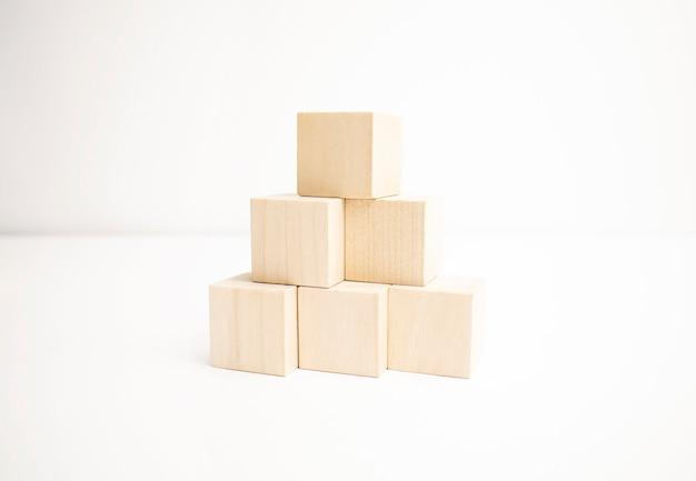 Blocos de madeira empilhados como uma escada em pirâmide em fundo branco.