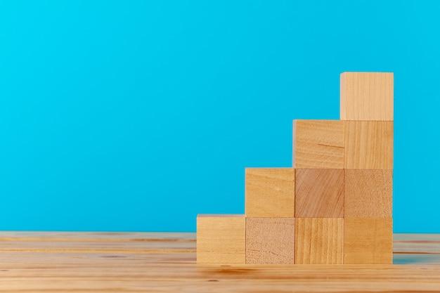 Blocos de madeira empilhados em uma mesa de madeira contra o azul