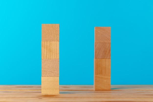 Blocos de madeira empilhados em uma mesa de madeira contra um fundo azul, copie o espaço