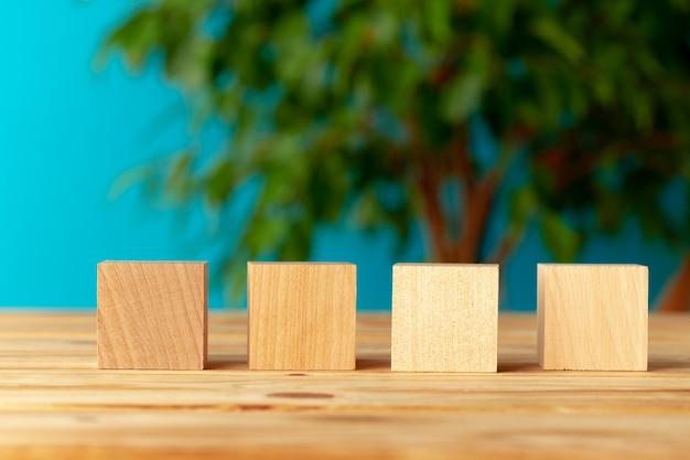 Blocos de madeira na mesa contra o fundo desfocado da planta