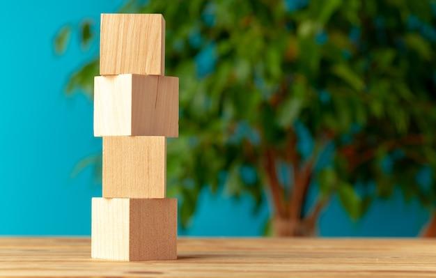 Blocos de madeira na mesa contra planta desfocada