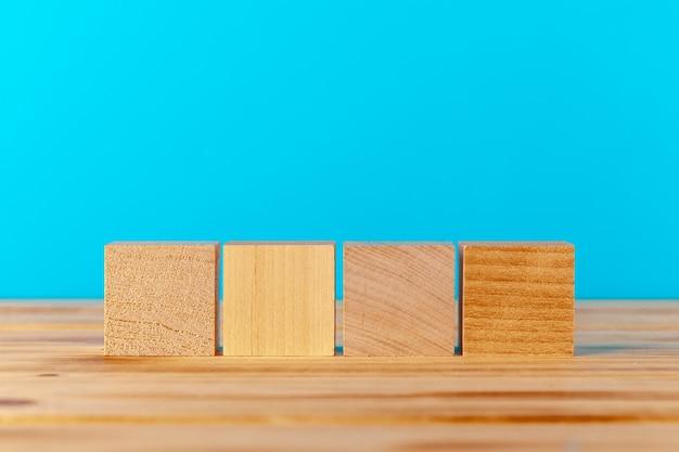 Blocos de madeira na mesa de madeira contra um fundo azul, copie o espaço