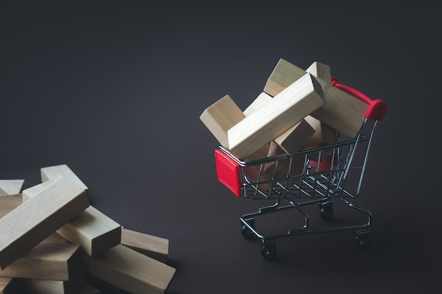 Blocos de madeira perto e no carrinho de compras em backg marrom. modelo com carrinho de compras, casa, blocos