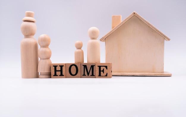 Blocos de madeira. soletrando casa, com pequena família de bonecas e pequena casa