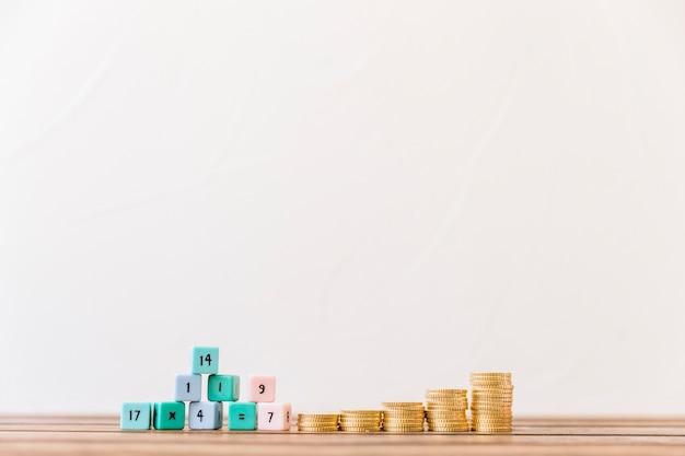 Blocos de matemática empilhados e moedas de ouro na mesa de madeira