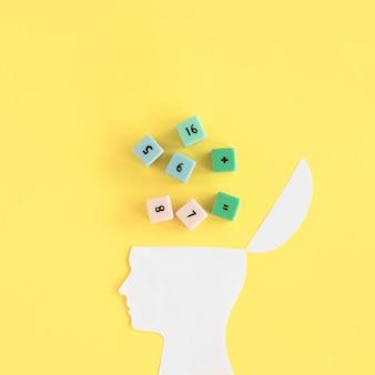 Blocos de matemática sobre o cérebro humano aberto em fundo amarelo