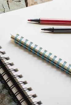 Blocos de notas e canetas