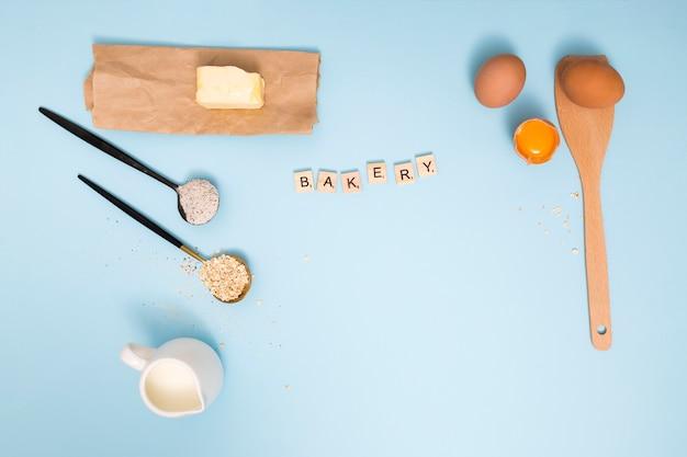 Blocos de padaria com manteiga; jarro de leite; celeiro de aveia; farinha; ovos e espátula de madeira no fundo azul