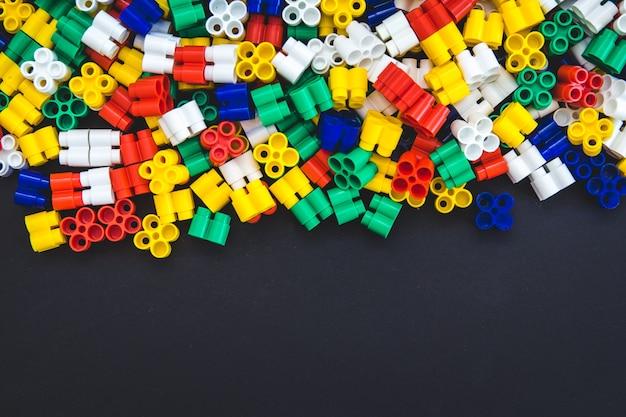 Blocos de plástico multicoloridos em um fundo preto com um lugar para texto