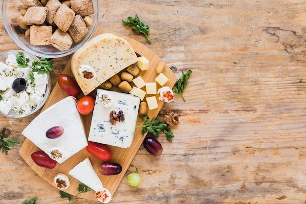 Blocos de queijo com tomate, salsa e uvas na mesa de madeira