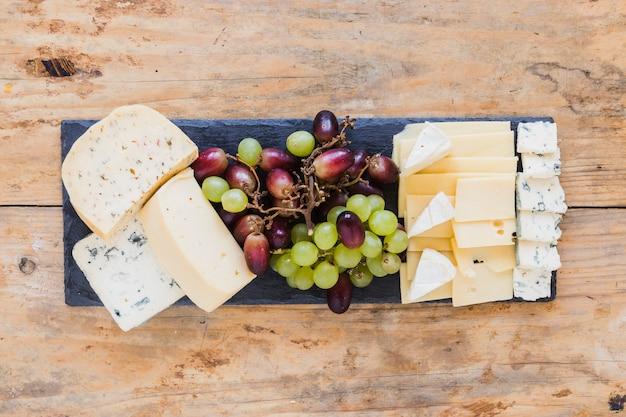 Blocos de queijo e fatias com uvas na lousa retangular sobre a mesa de madeira