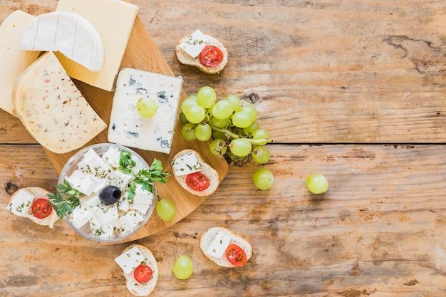 Blocos de queijo e uvas com pão na mesa de madeira