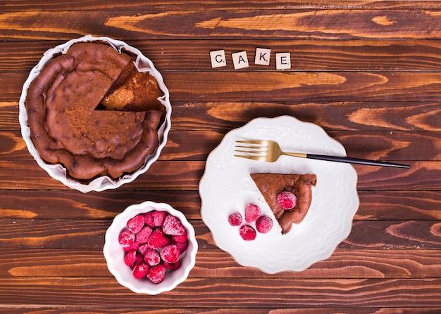 Blocos de texto de bolo sobre o bolo de fatia e framboesa na chapa branca com garfo