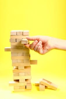 Blocos do jogo de madeira em um fundo amarelo